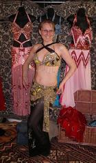 Trillian of the Daughters of Rhea Dance Ensemble tries on a gold and black costume