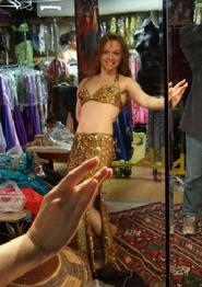 Piper tries on a gold two piece number at Shahrzad's Belly Dance Store