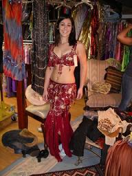 Amelia of the Baltimore Daughters of Rhea Belly Dance Ensemble tries on a red two piece costume