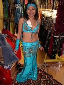 Rowina of the Baltimore Daughters of Rhea Daughters of Rhea Dance Ensemble tries on a two piece turquoise costume