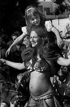 Rhea dancing with Piper on her shoulders and Melinda in her belly at the 1969 Berkeley Fiddler's Convention